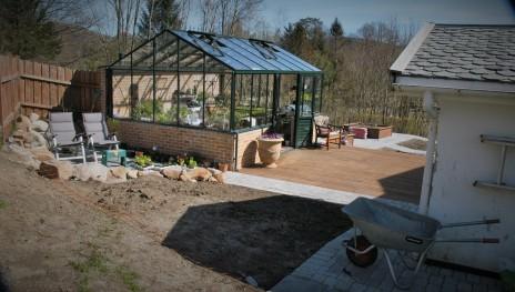 Drivhuset og den uferdige hagen fra en annen vinkel.